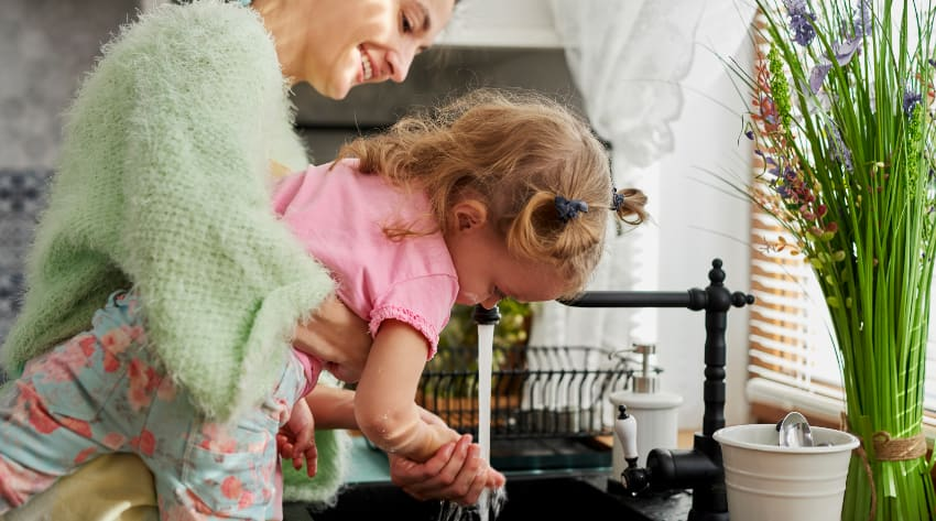 Mother and toddler daughter washing their hands in the kitchen sink