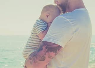 Man holding newborn baby to his chest
