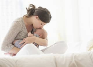 woman siting crossed legged while comforting and kissing a newborn on the forehead