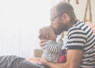 Man kissing baby on the forehead