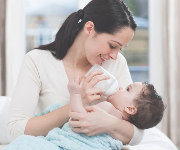 Woman bottle feeding a baby in her arms