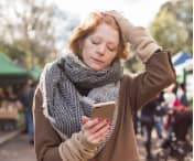 Stressed woman holding a phone with her eyes closed